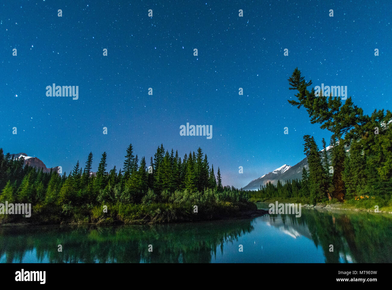 Caption of the North: starry sky in the Bow river valley in Banff national park. Mountains and trees reflected in the blue waters. Campsite, tent. Stock Photo
