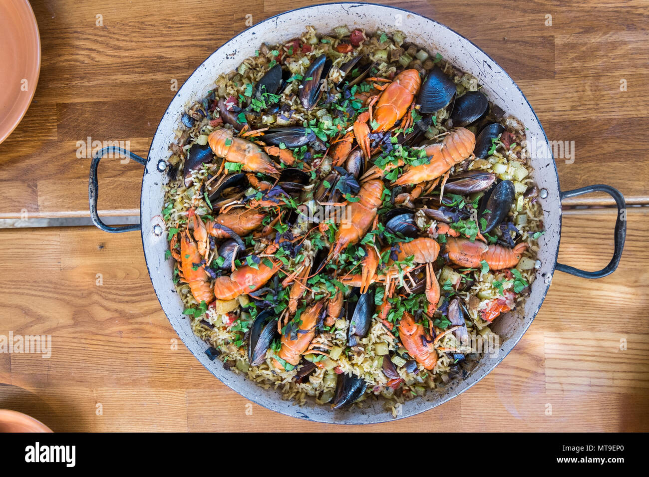 Spanish seafood Paella with Prawns Mussels and ?rayfish on wood table - Stock Image