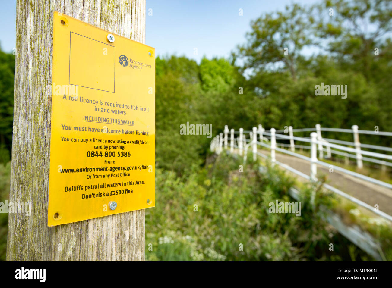 An Environment Agency sign warning anglers that they need to purchase a rod licence to fish in inland waters in the UK or face a fine if caught withou - Stock Image