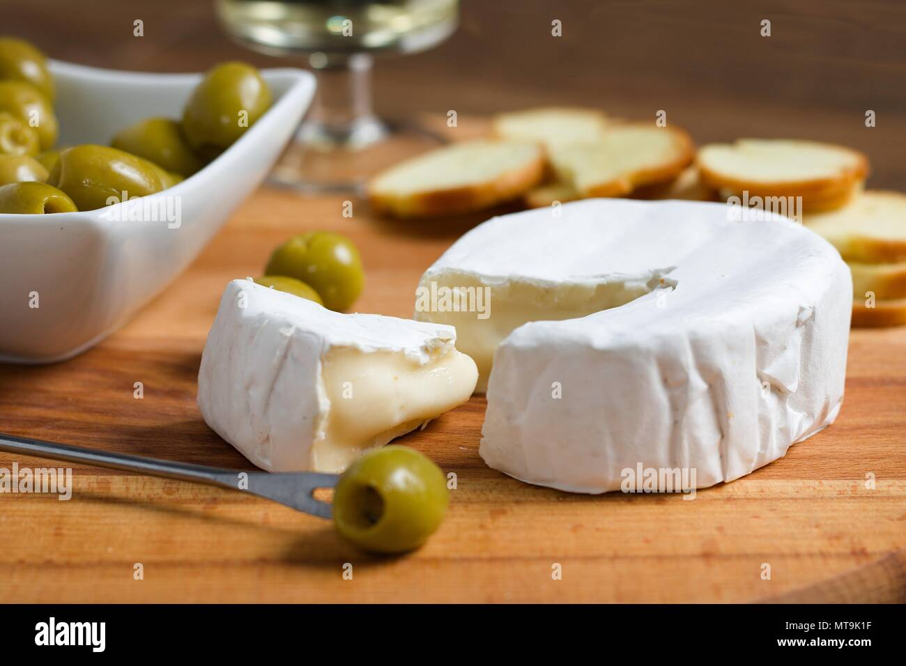 Soft Cheese With White Rind Camembert Or Brie On Wooden Board With Roasted Bread Slices Olives And White Wine Stock Photo Alamy
