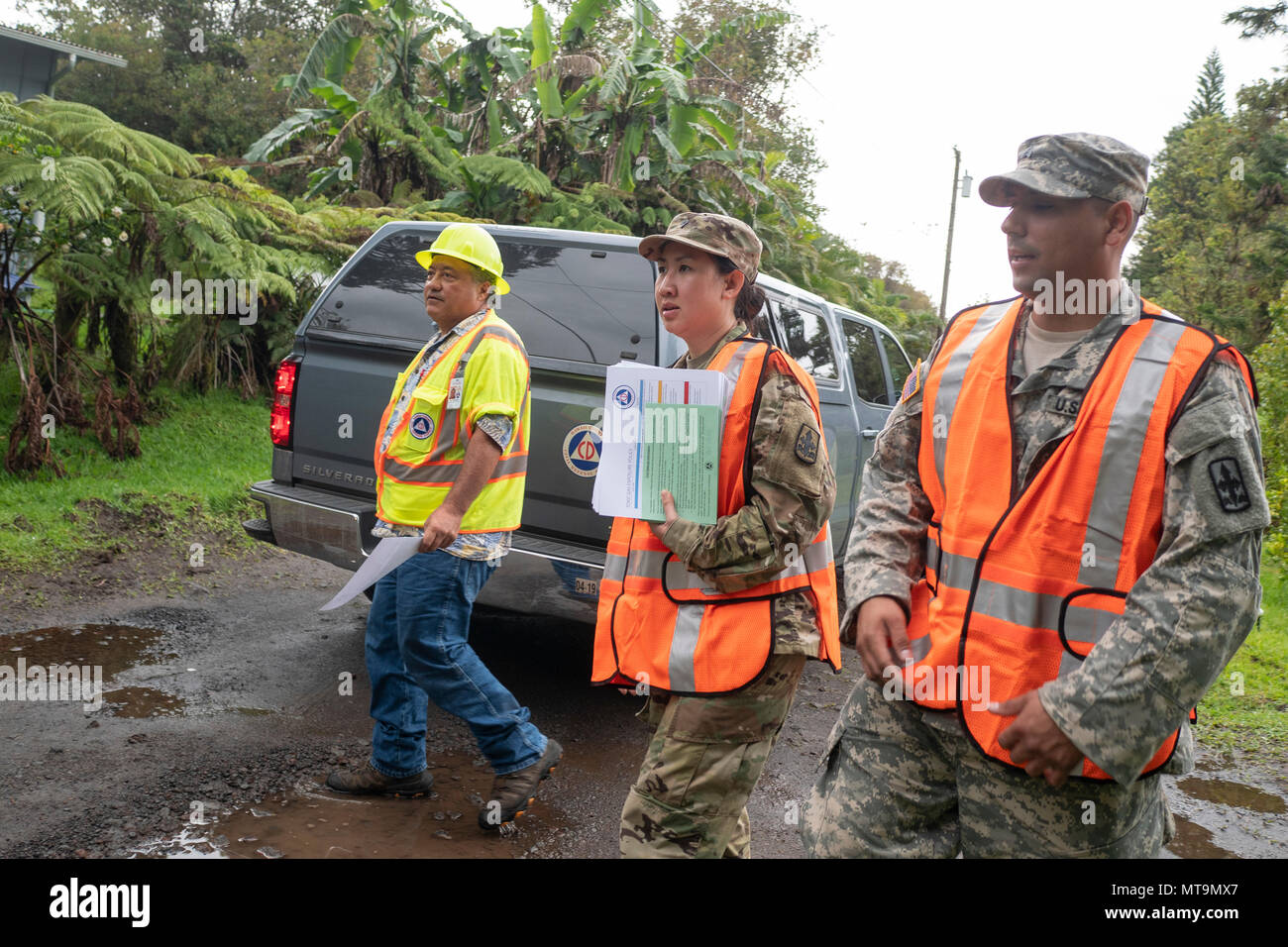 William Hanson, County of Hawaii Civil Defense administrative officer, Spc. Anyanee Sangchan and Sgt. Ambrose Leon, representatives of Task Force Hawaii, approach residents of the Volcano community May 17, 2018, at Upper Puna District, Hawaii. Teams went door-to-door to inform local residents of the heightened risks, due to the ongoing volcanic activity in the area. (U.S. Air National Guard photo by Senior Airman John Linzmeier) - Stock Image
