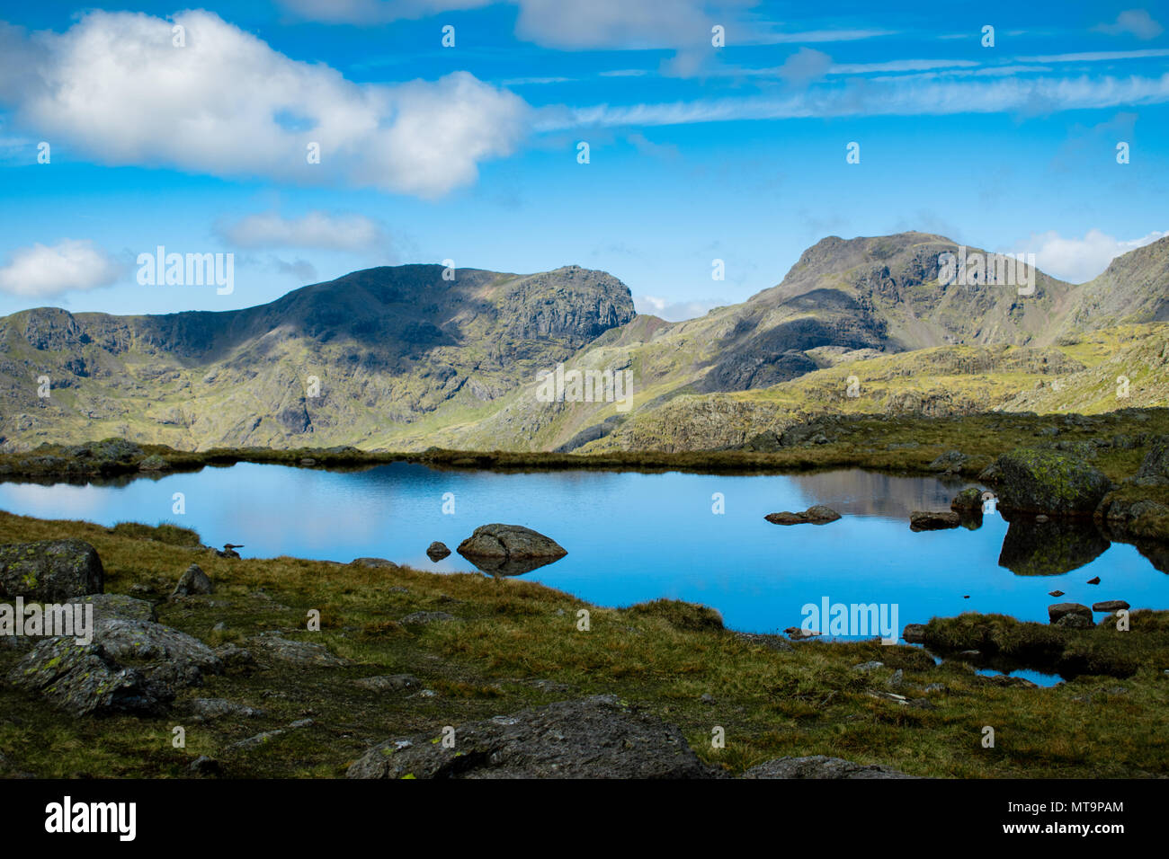 View of Scafell Pike from the South East with the mountain reflected in a nearby body of water under a cloudy sky. Scafell Pike is to the right. - Stock Image