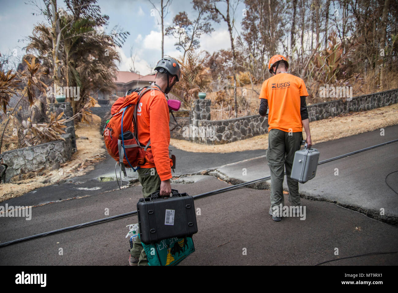 Pāhoa, Hawaii, May 19, 2018 – U.S. Geological Survey (USGS) volunteer Allen Lerner (left) and USGS Research Scientist Christoph Kern (right) prepare to use sulfur dioxide (SO2) sensors to monitor and test the air quality after the Kīlauea volcanic eruption. The residential area of Leilani Estates has been evacuated due to the high concentration of SO2 emitting from the cracks in the earth that spilled lava into the subdivisions. At the request of the state, FEMA staff are on the ground to support local officials with life-saving emergency protective measures, debris removal, and the repair, re - Stock Image