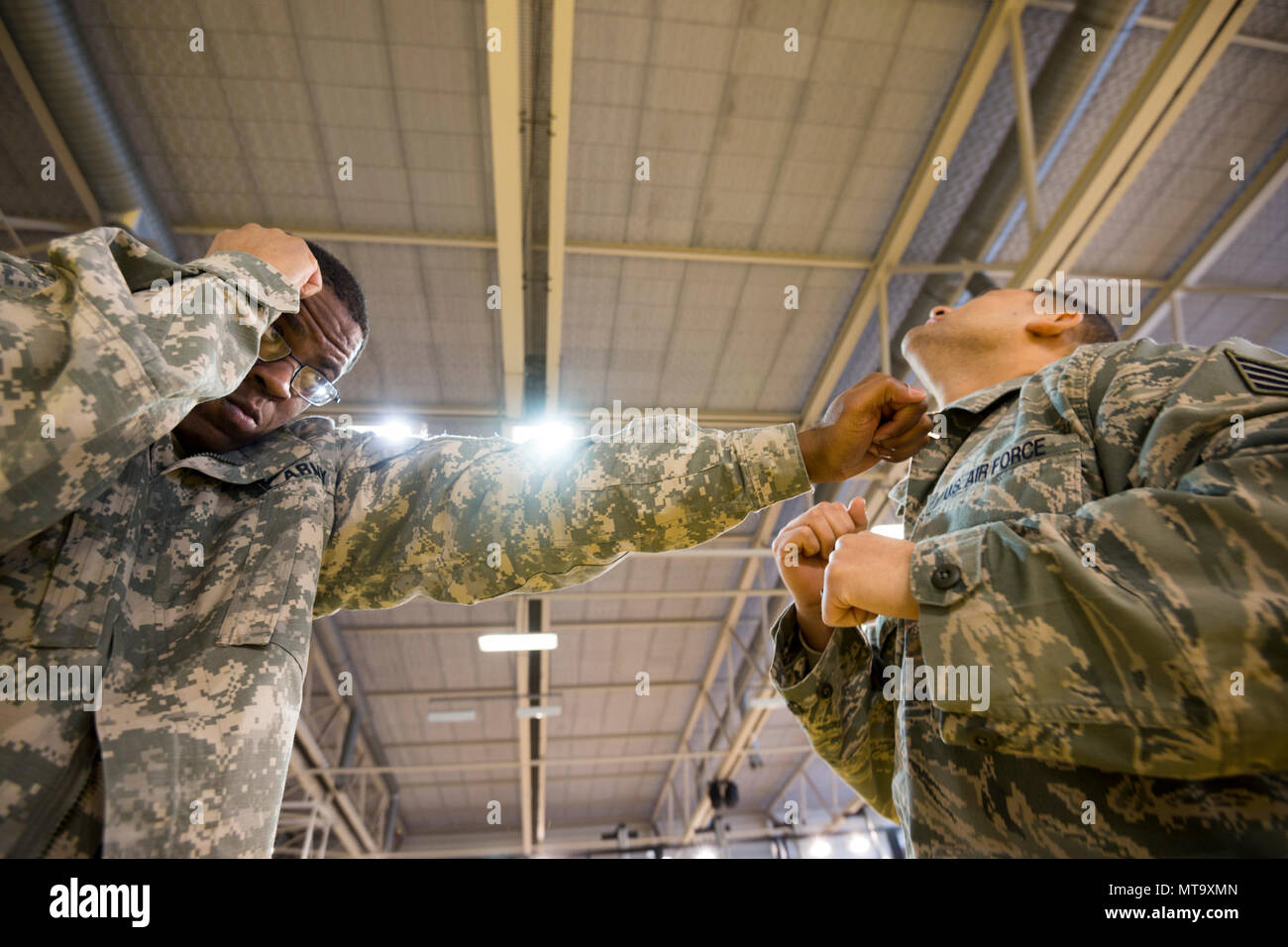 U.S. Army Sgt. Terrance Simmons, assigned to the Northern Law Center, 21st Theater Sustainment Command, demonstrates how to punch on U.S. Air Force Staff Sgt. Mario Huerta, assigned to the SACEUR Security Detachment, during the   Joint Tactical Combatives Course, on Chièvres Air Base, Belgium, March 9, 2018. - Stock Image