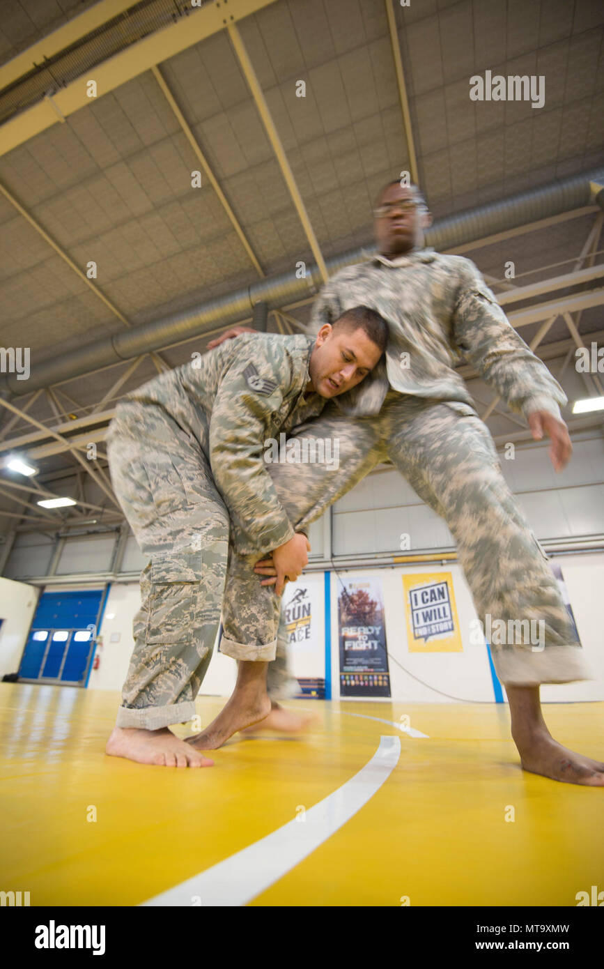 U.S. Air Force Staff Sgt. Mario Huerta (left), assigned to the SACEUR Security Detachment, grabs the leg of U.S. Army Sgt. Terrance Simmons, with the Northern Law Center, 21st Theater Sustainment Command, during the  Joint Tactical Combatives Course, on Chièvres Air Base, Belgium, March 9, 2018. - Stock Image