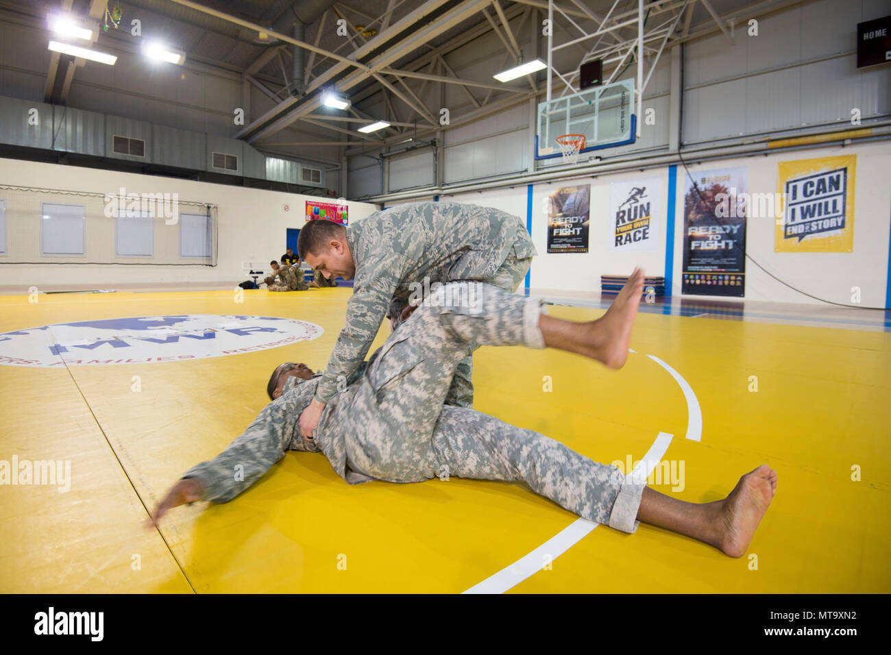 U.S. Air Force Staff Sgt. Mario Huerta, right, assigned to the SACEUR Security Detachment, controls the landing, after a hip throw, of U.S. Army Sgt. Terrance Simmons, with the Northern Law Center, 21st Theater Sustainment Command, during the Joint Tactical Combatives Course, on Chièvres Air Base, Belgium, March 9, 2018. - Stock Image