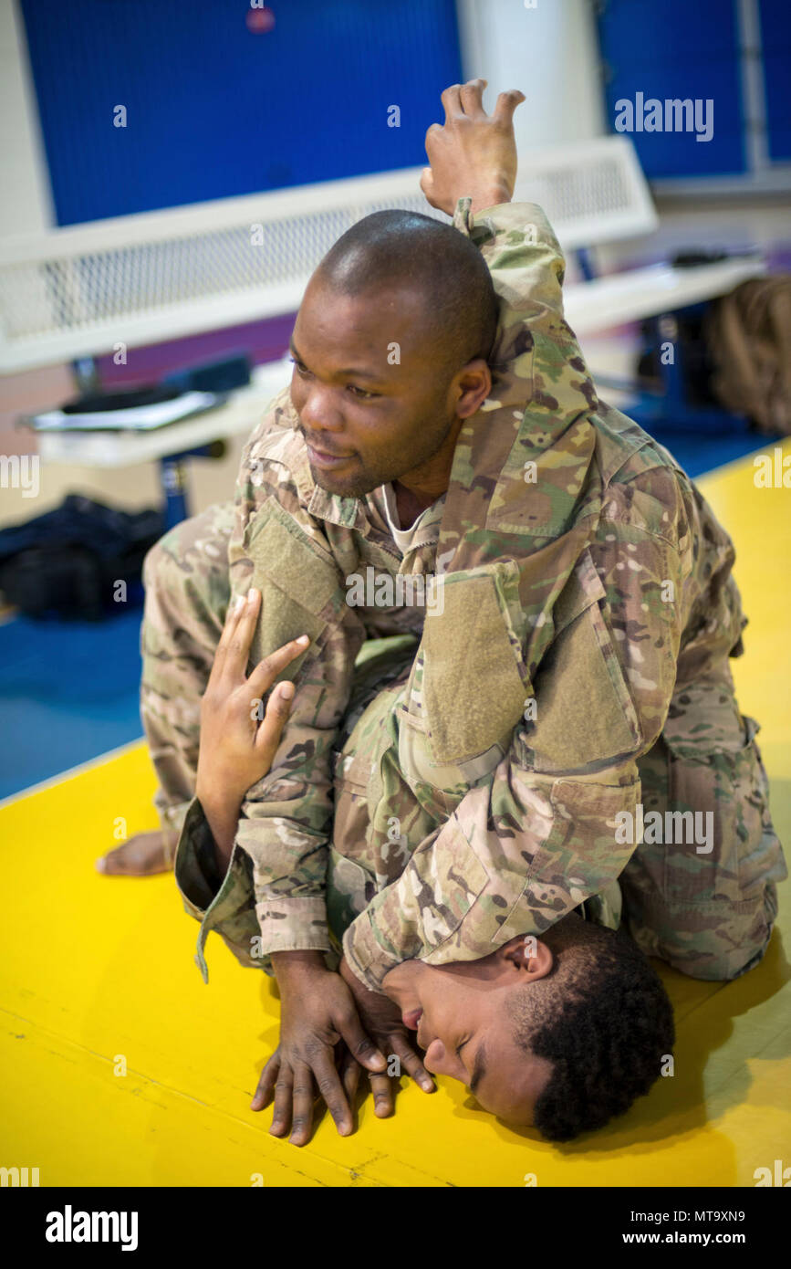 U.S. Army Staff Sgt. Richard Amoah, assigned to Benelux Finance, 226th Financial Management Support Center, 21st Theater Sustainment Command, escapes the headlock from Pfc. Henry Tillman, with Headquarters and Headquarters Detachment, 39th Strategic Signal Battalion, during the Joint Tactical Combatives Course, on Chièvres Air Base, Belgium, March 9, 2018. - Stock Image