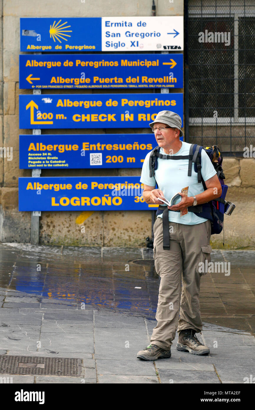 Pilgrim looking for directions next to directional signboards for hostels, Camino de Santiago, Logroño, La Rioja, Spain - Stock Image