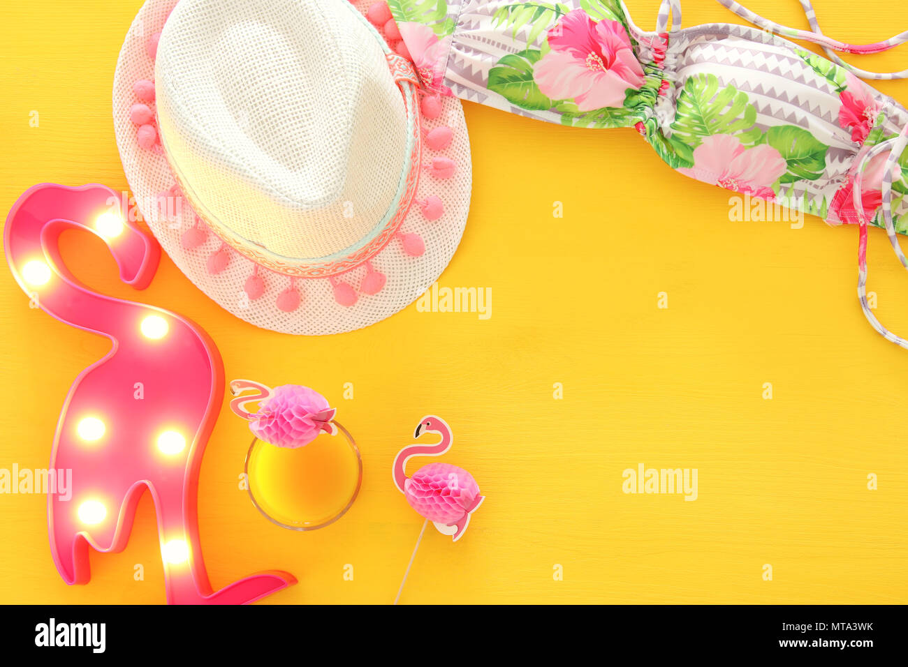 9ca4821080 Top view of fashion female swimsuit bikini and white fedora hat on yellow wooden  background. Summer beach vacation concept