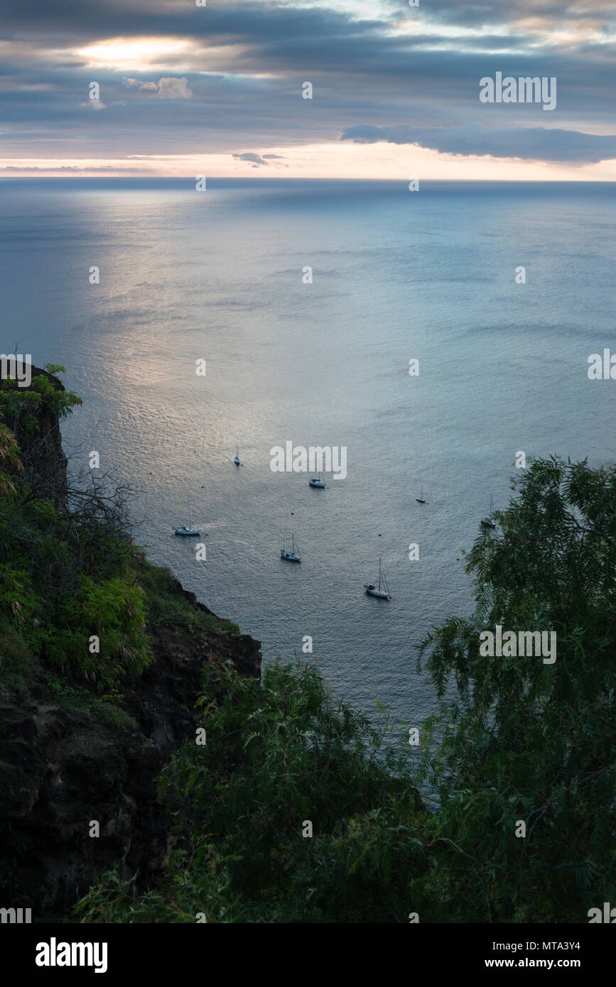 Cruising yachts on the well maintained mooring buoys off Jamestown at dusk, in the lee of the remote tropical island of St Helena, South Atlantic - Stock Image