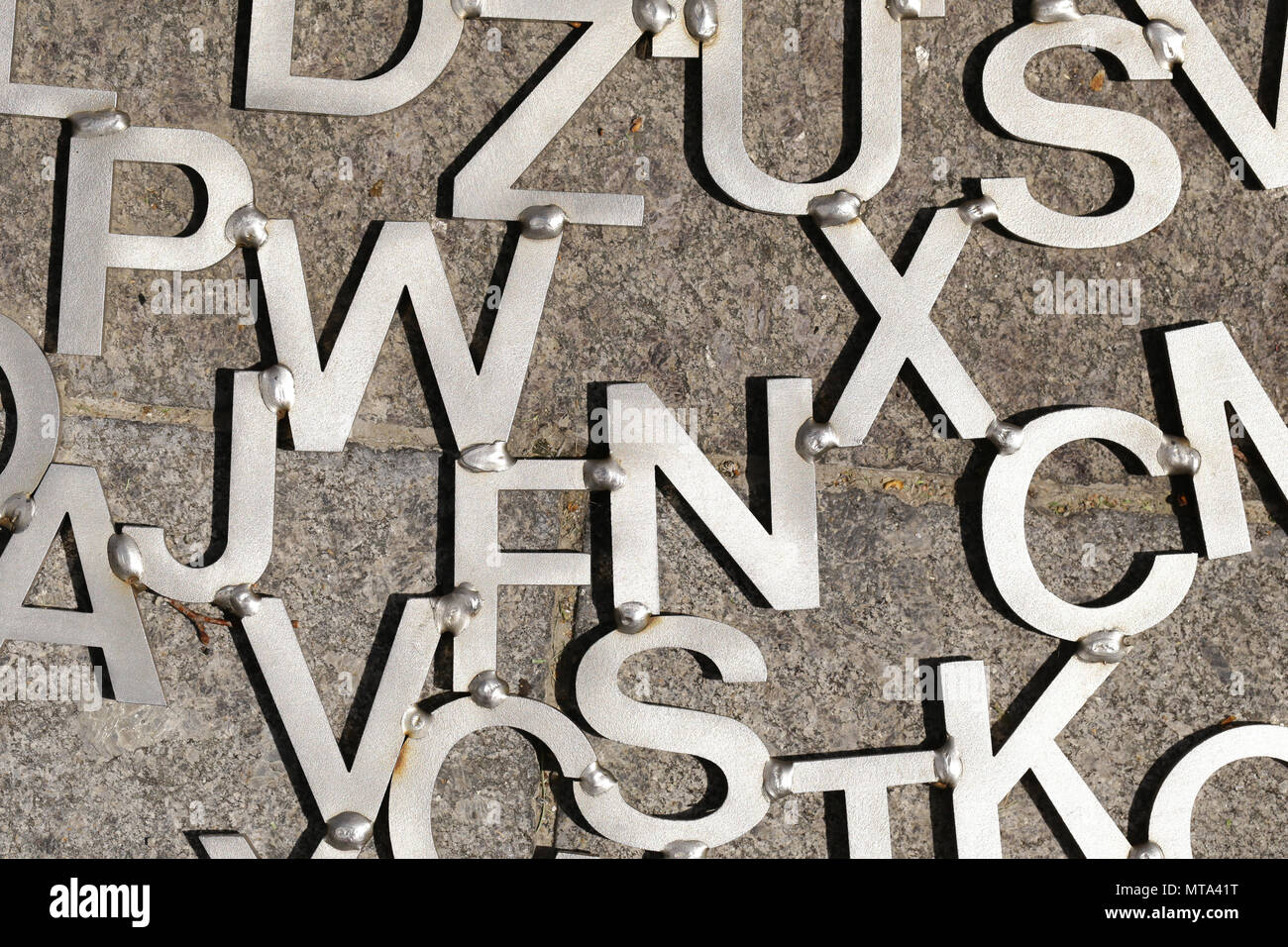 old metal letters on a gray background - Stock Image
