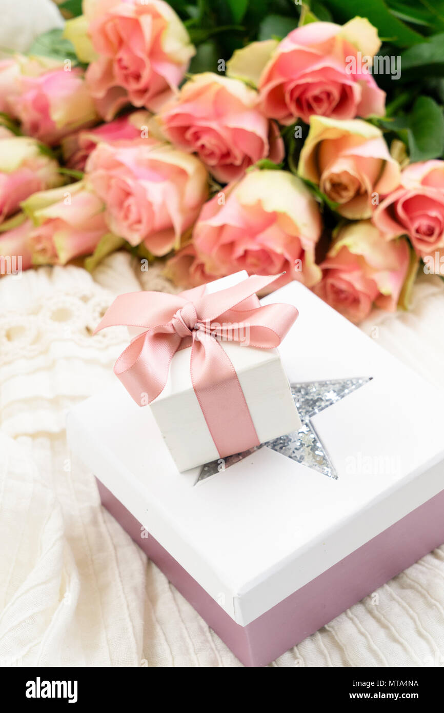 Pink Roses Bouquet With Pile Of Gift Boxes On Wedding Dress