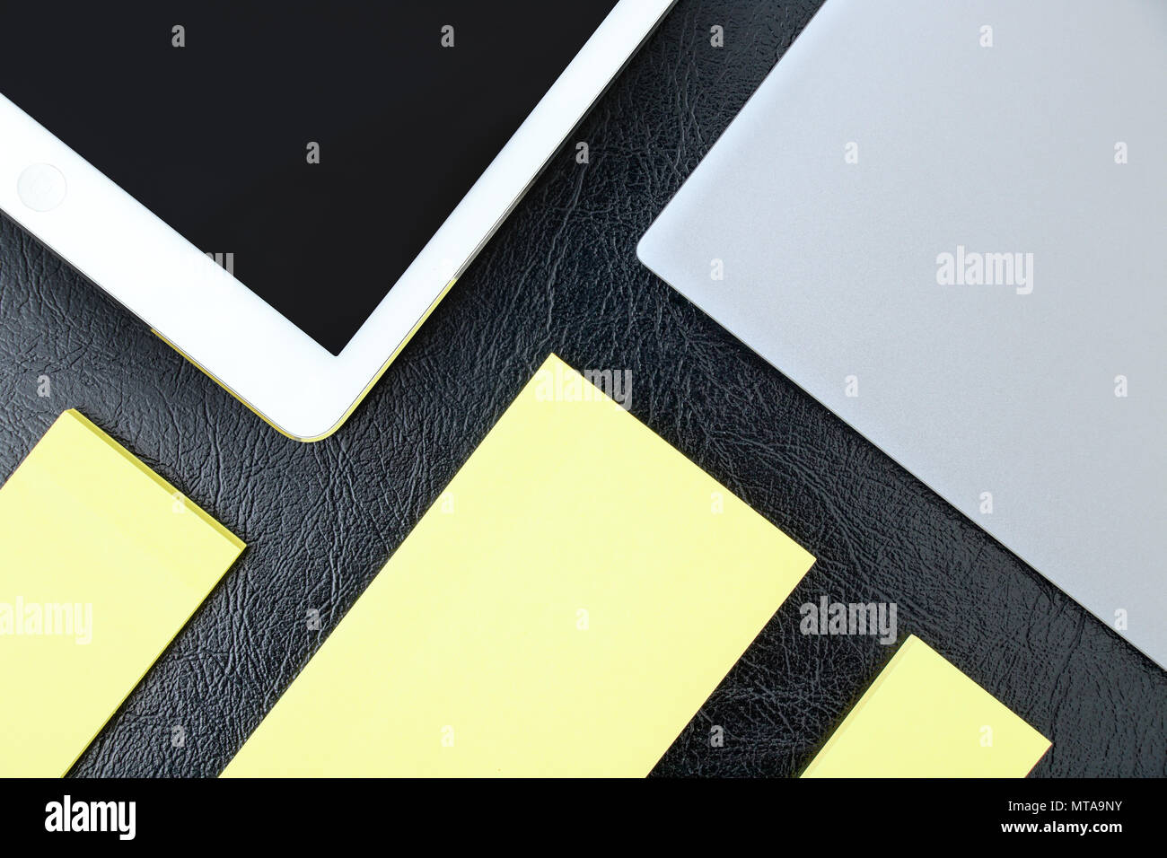 Overhead of office table with notebook, tablet pc and yellow notepad copy spaces - Stock Image