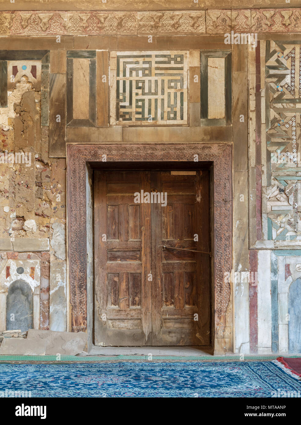 Grunge wooden decorated door on external old decorated marble wall, El Mardani Mosque, Cairo, Egypt - Stock Image