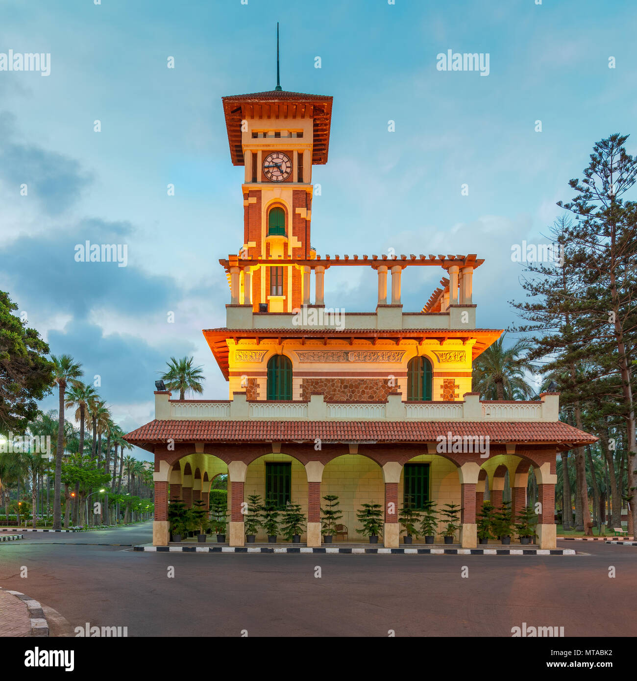 Facade of the clock tower in Montaza public park with decorated stone wall, green wooden window shutters, and red tile canopies at sunrise time, Monta - Stock Image