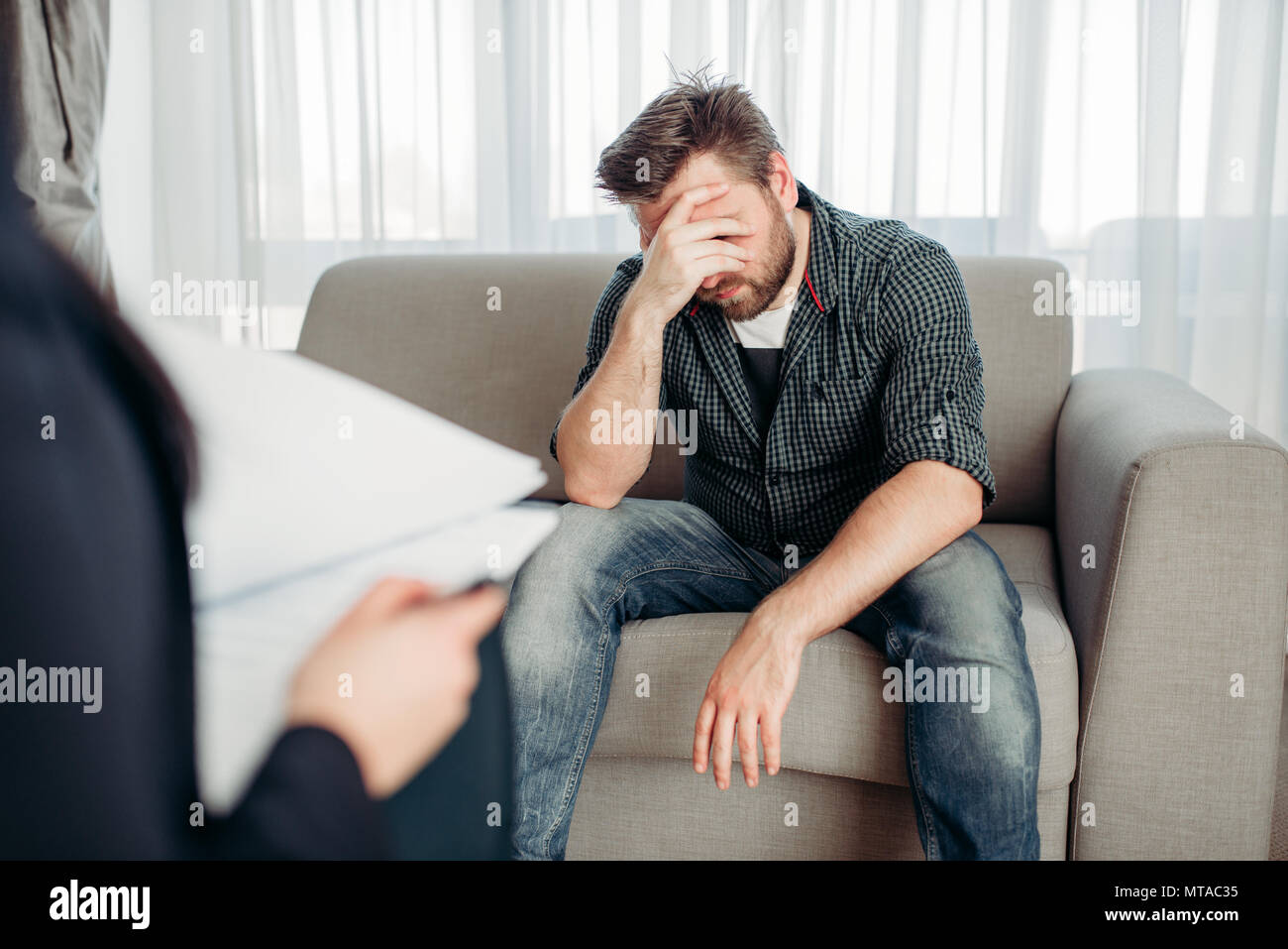 Stressed male patient at psychologist, professional psychology support. Female doctor writes notes in notepad, man sitting on sofa Stock Photo