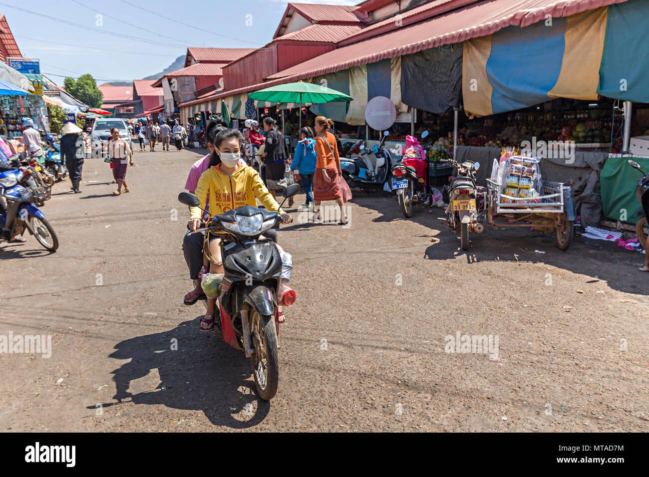 Woman warking face mask riding scooter through market, Pakse, Laos - Stock Image