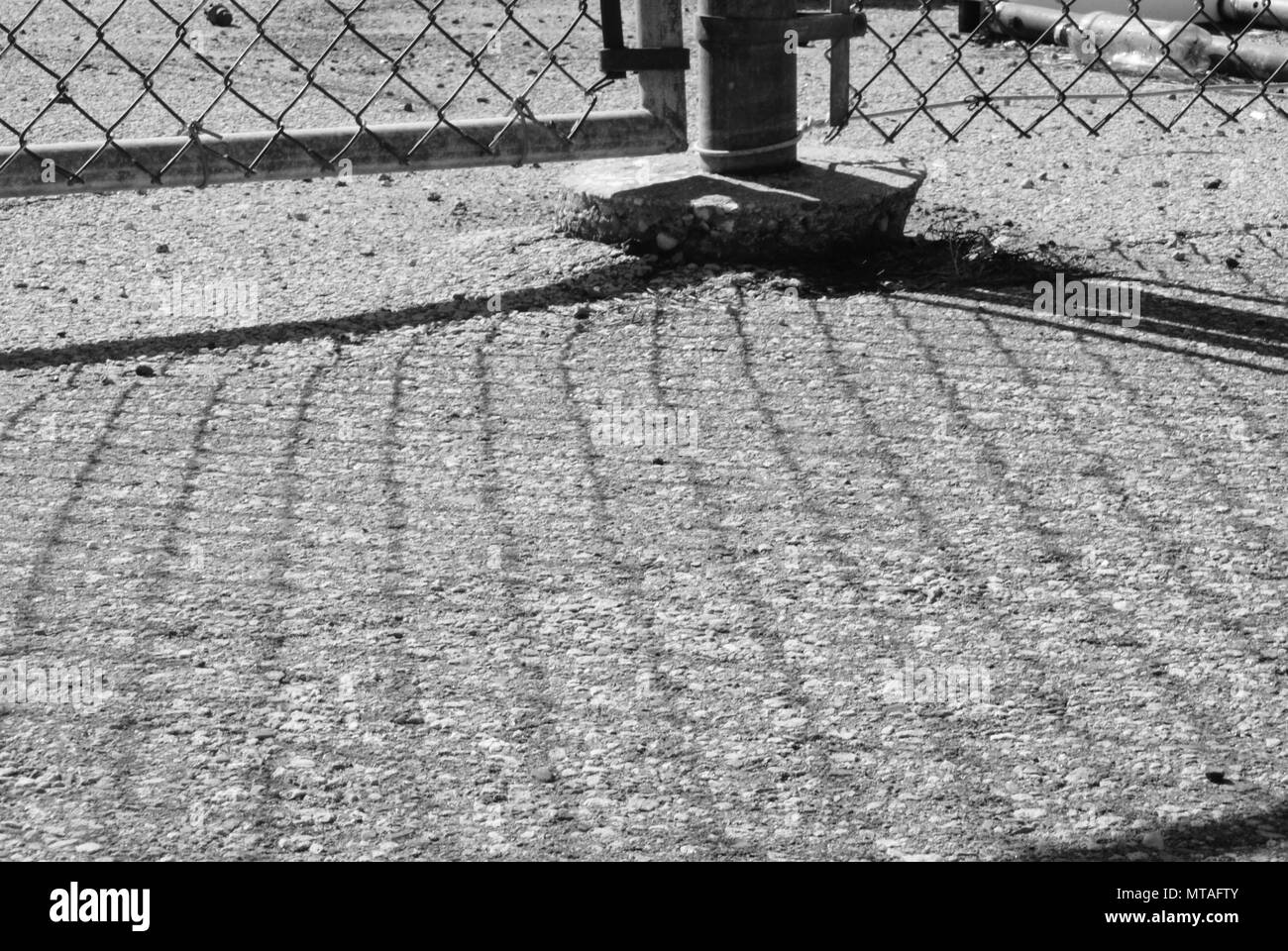 Paved ground with the shadow of a wire fence over it. - Stock Image
