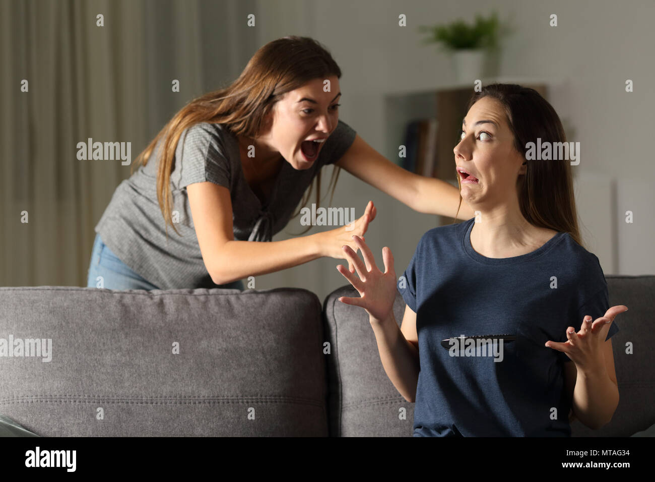 Woman giving a fright to a friend sitting on a couch in the living room at home - Stock Image