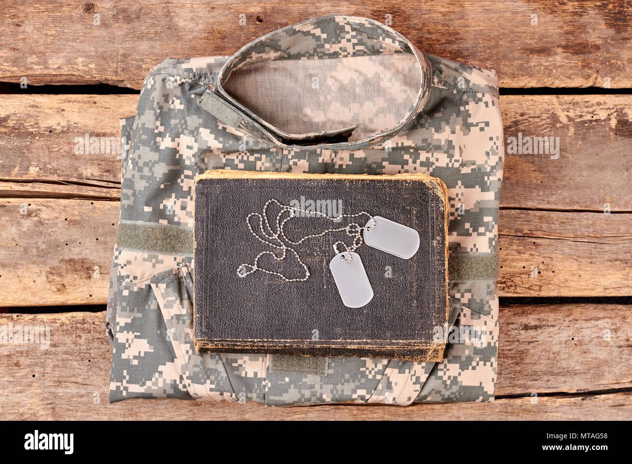 Camouflage army clothes, book, and dog tags on wood. Flay lay, top view. Stock Photo