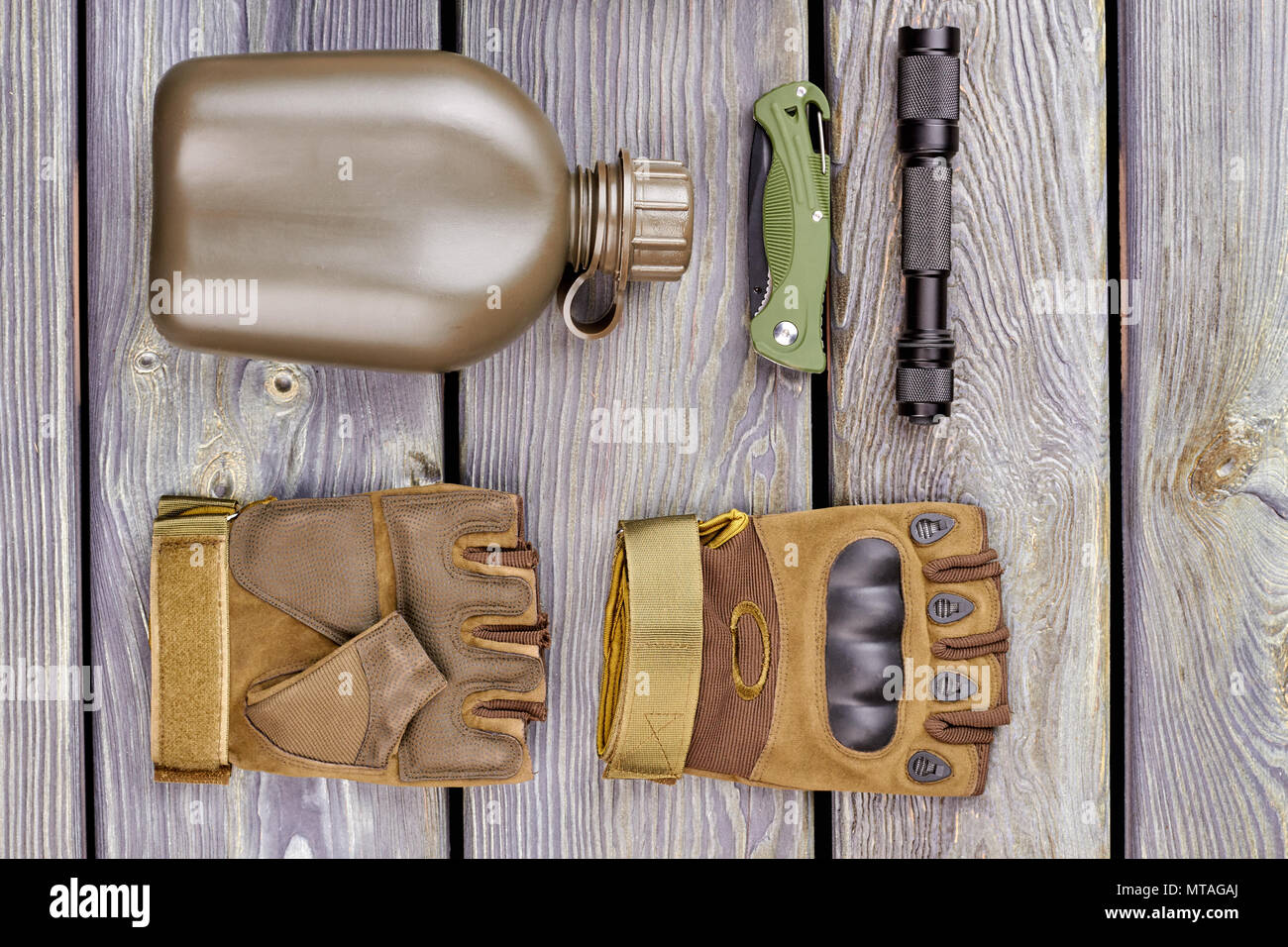 Military bottle, pair of gloves, pocketknife and torch. Wooden desk background. - Stock Image