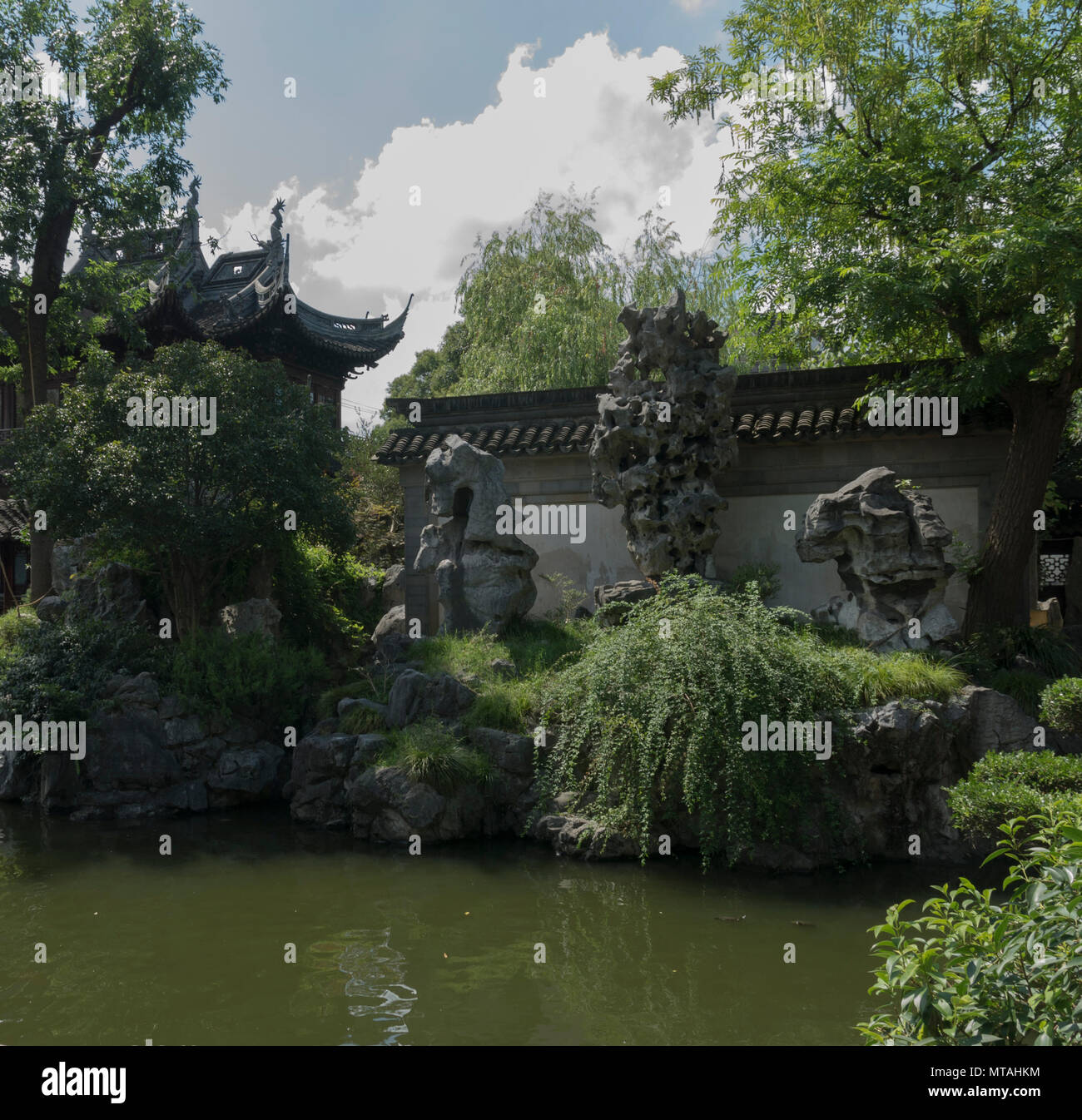 Yu Gardens Shanghai China Beautiful Day blue sky, natural formed rocks to complement fish pond, - Stock Image