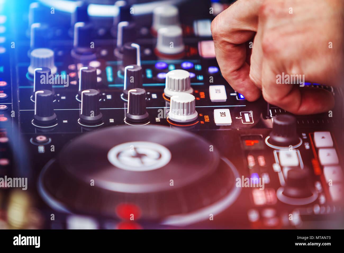 disk jockey playing music at mixer - Stock Image