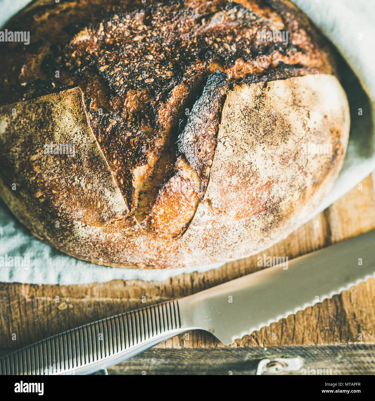 Freshly baked sourdough bread on chopping board, square crop Stock Photo