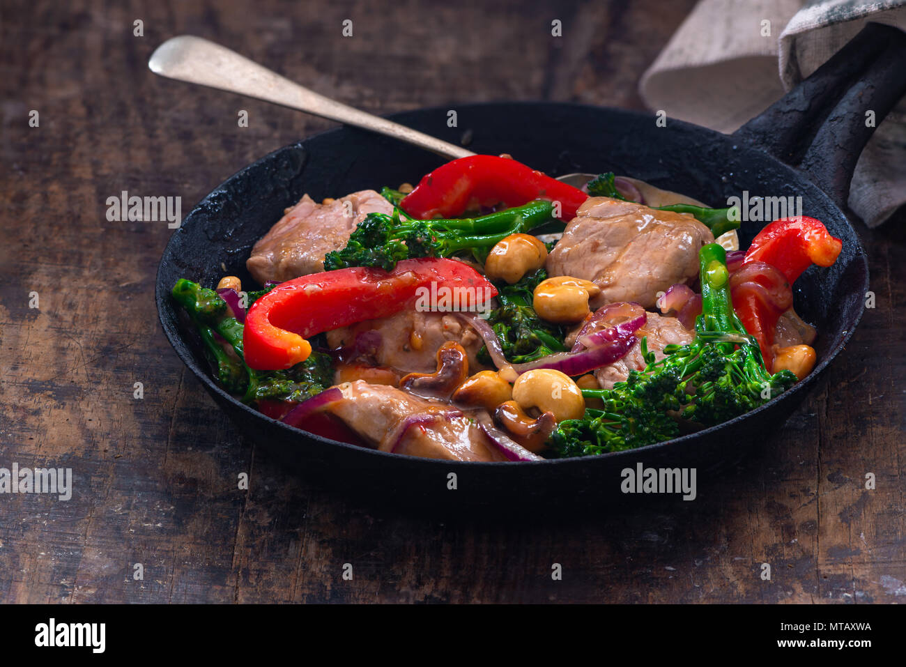 Sichuan pork, broccoli, red pepper and cashew stir-fry in a frying pan Stock Photo