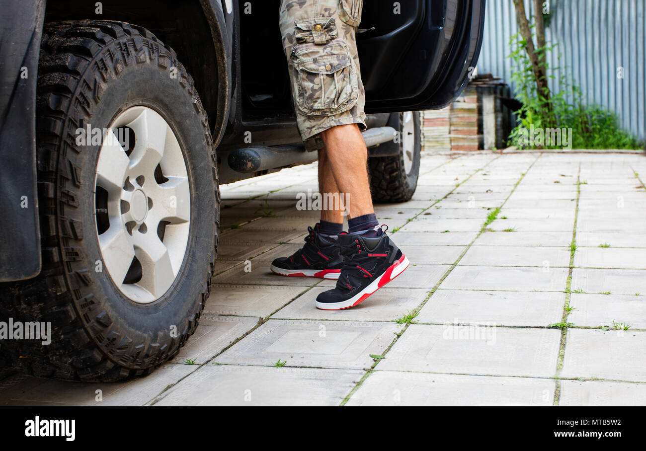 Man in camo shorts standing next to the truck with open door. - Stock Image