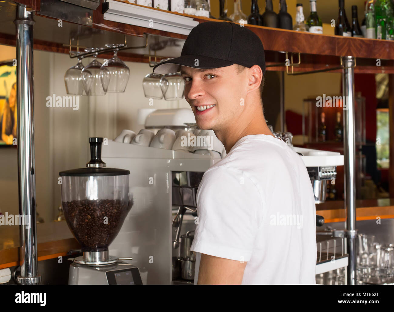 Young handsome smiling barista in white shirt and baseball hat s - Stock Image