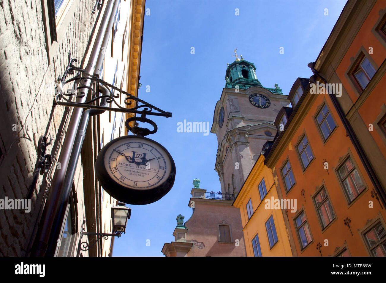 A clock used as a shop sign for Mobel Hansson, which is an antique shop on Storkyrkobrinken, Gamla Stan, Stockholm, Sweden - Stock Image