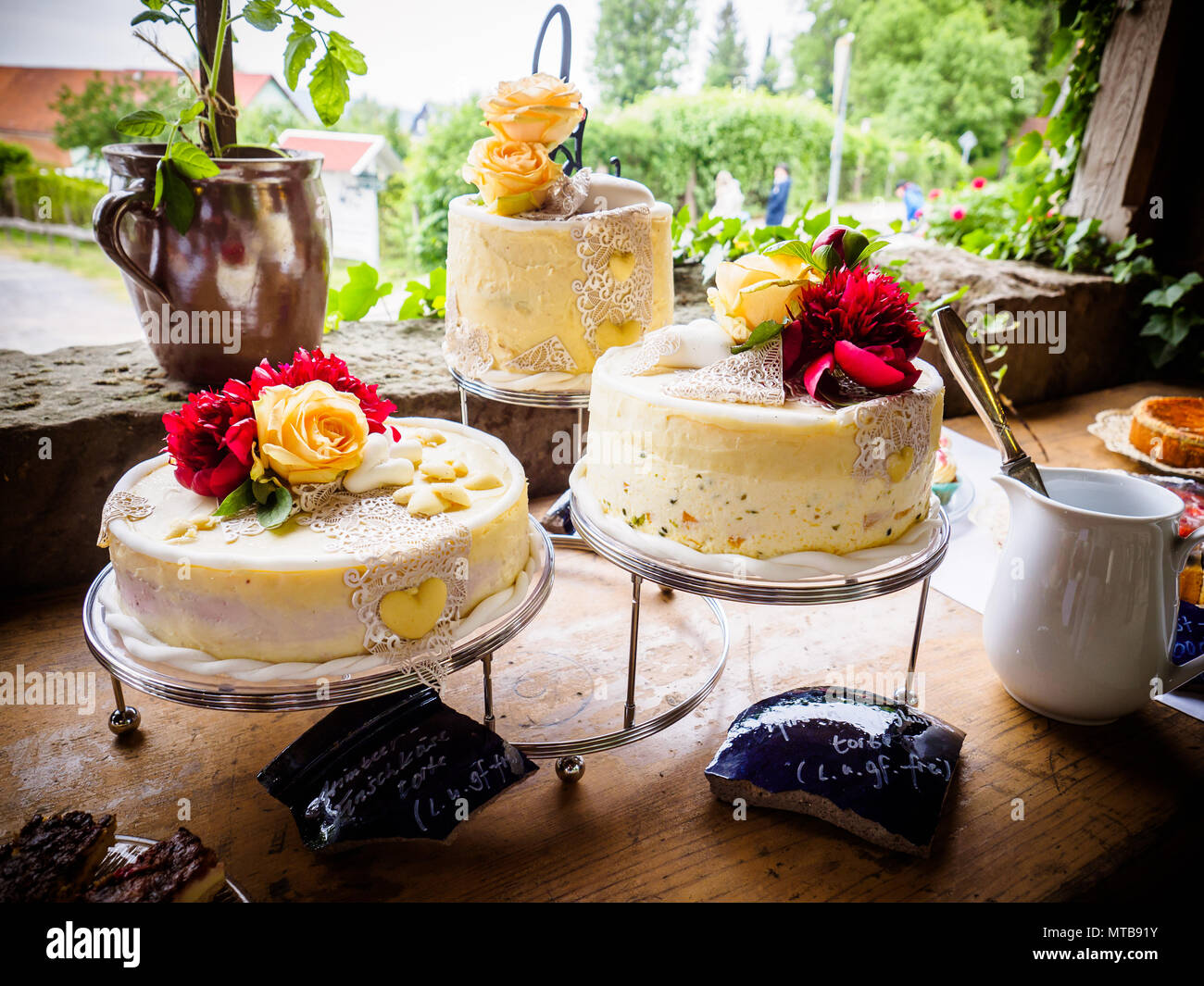 White wedding cake and sweets decorated with natural flowers - Stock Image