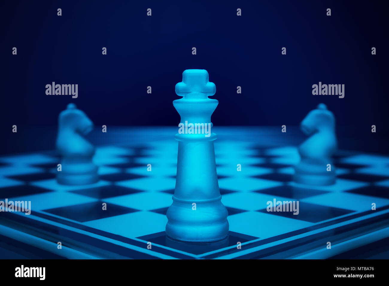 Chess game. King on the battle field with two knights. Stock Photo