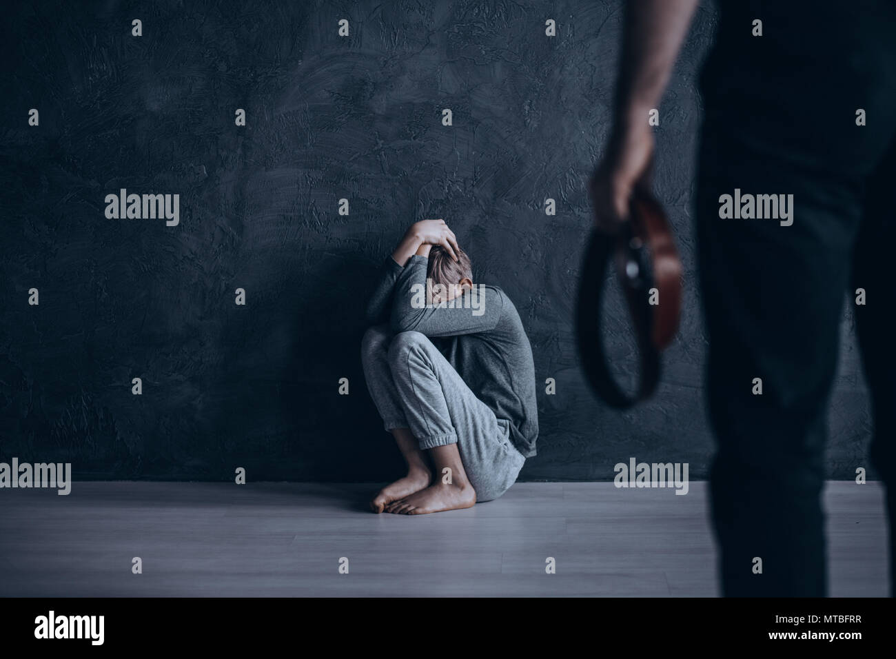 Heartbreaking, conceptual photo of son beaten by his own father - Stock Image