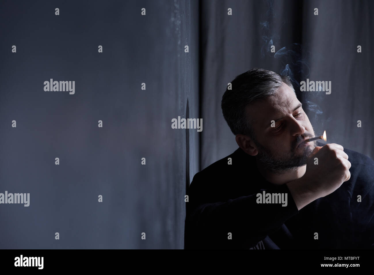 Broken smoking man having depression because of separation - Stock Image