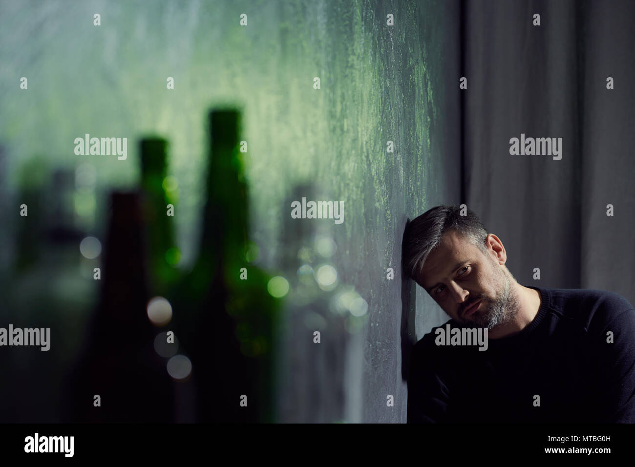 Man suffering from depression with empty alcohol bottles - Stock Image