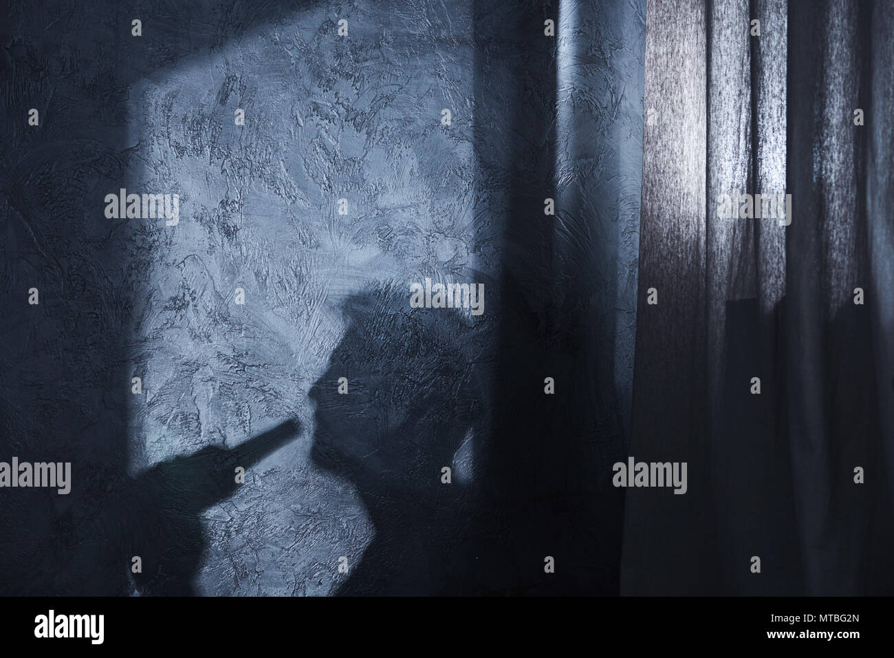 Shadow of drinking man on the wall - Stock Image