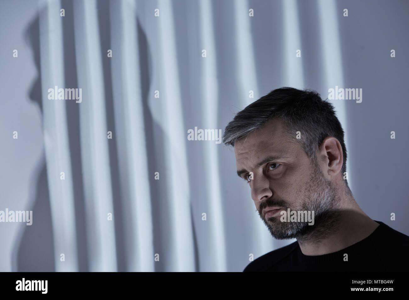 Broken man with depression in room interior - Stock Image