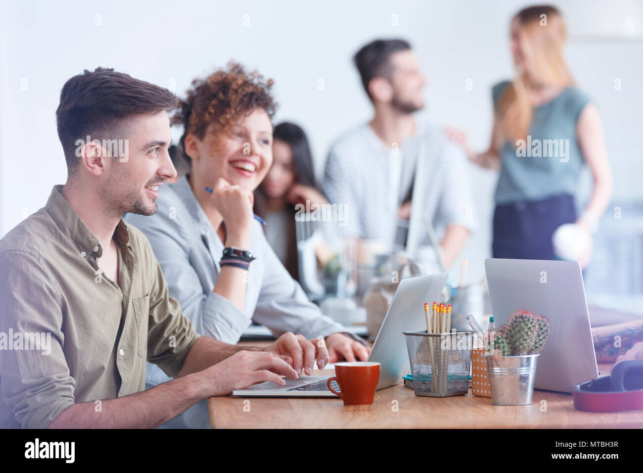 Group of colleagues at a coffee break having an interesting discussion - Stock Image