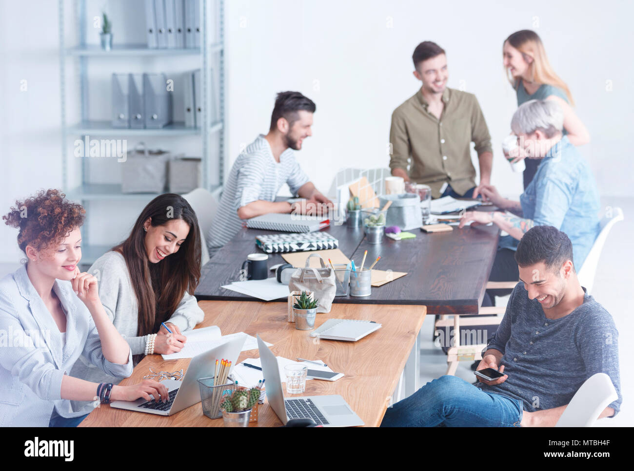 Culturally diverse team of employees enjoying their time on a break - Stock Image