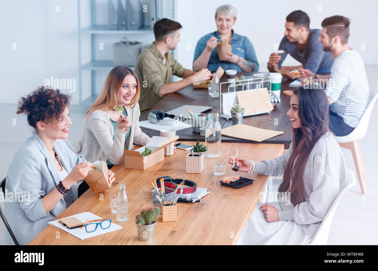 Colleagues chatting about a new concept in the office, during lunch break - Stock Image