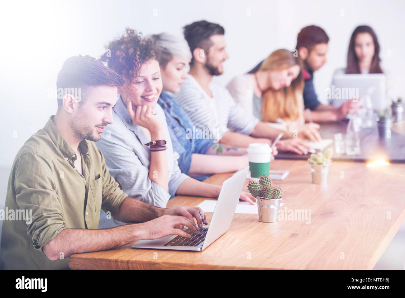 Employees at work in a modern office, enjoying laid back atmosphere - Stock Image