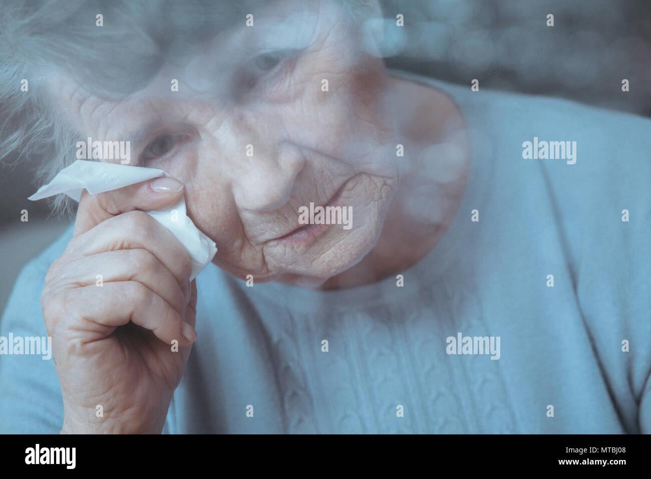 Portrait of sad, lonely senior woman crying, holding tissue - Stock Image