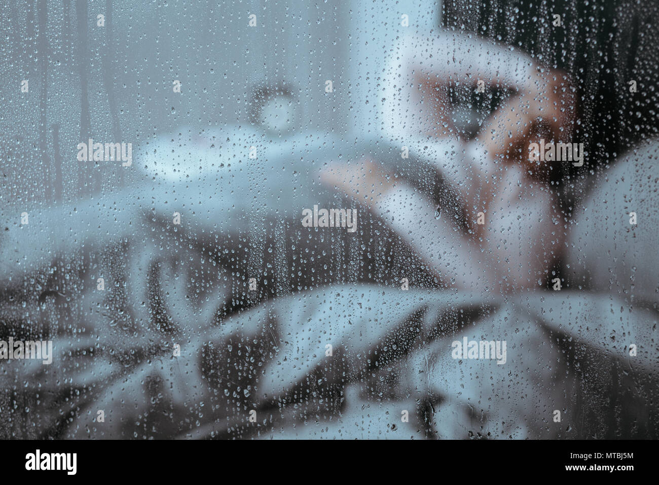 Woman suffering from sleeplessness lying in bed on rainy day - Stock Image