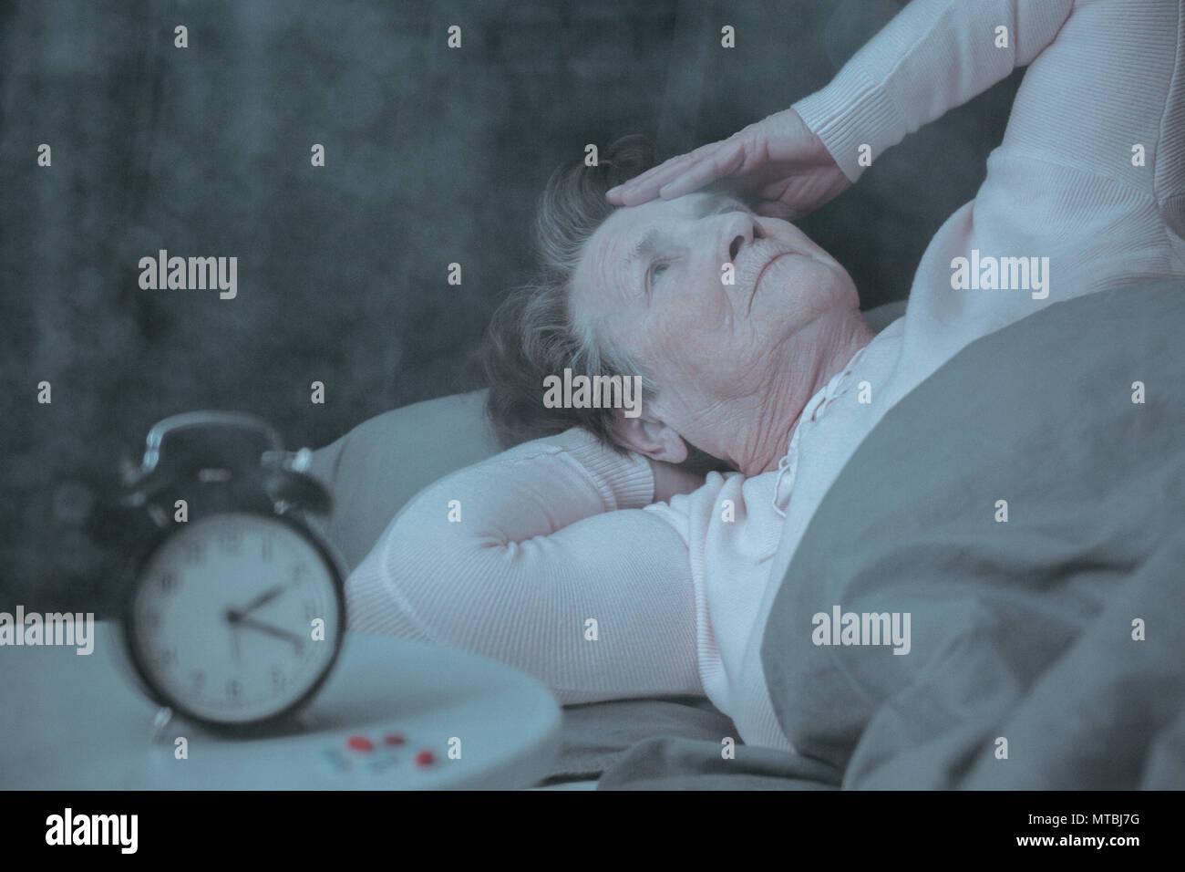Senior woman having sleep disorder, lying in bed - Stock Image