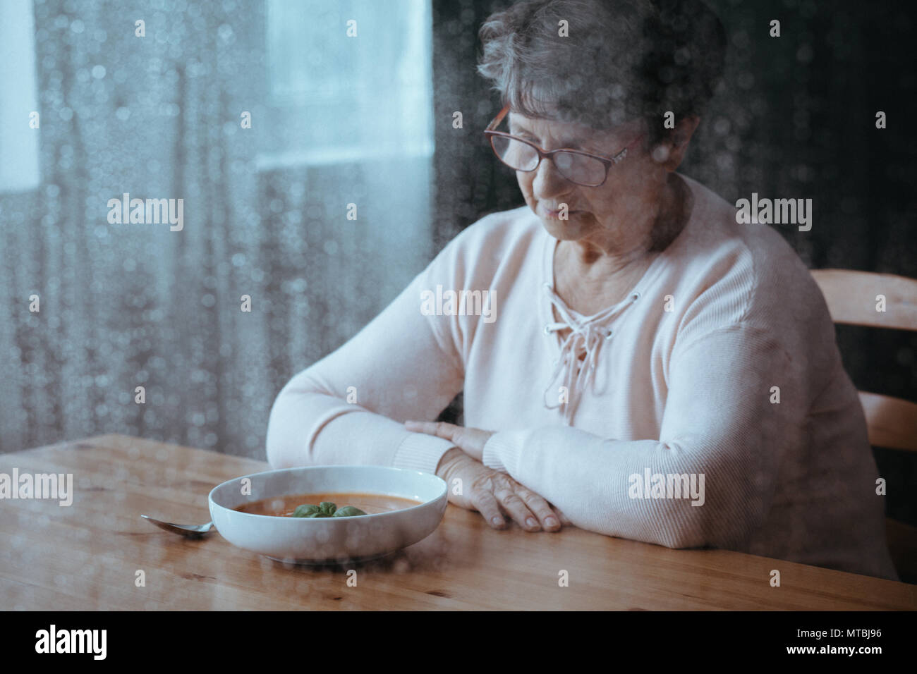 Sad, senior woman having lack of appetite - Stock Image