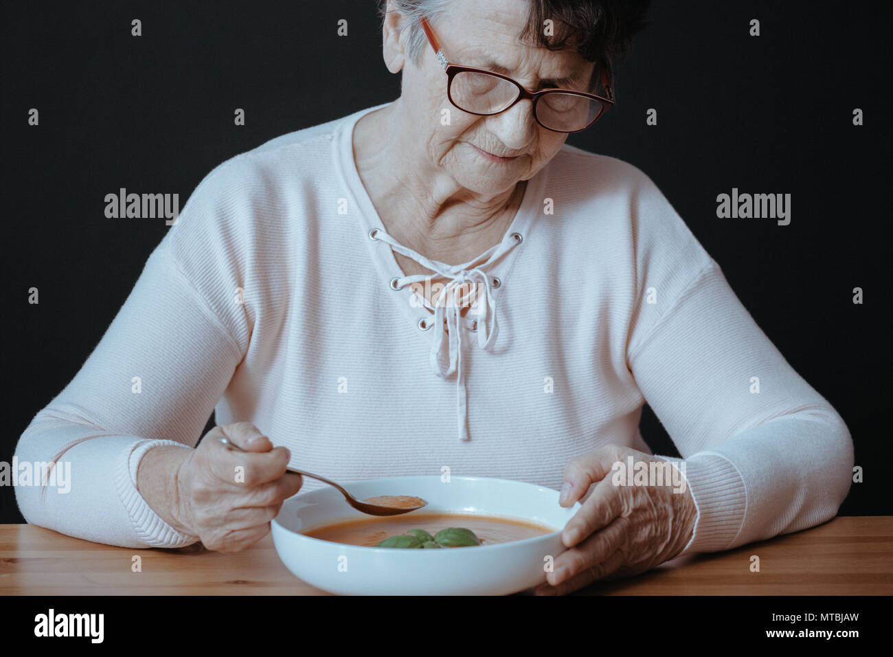 Senior woman suffering from inappetence, sitting beside table - Stock Image