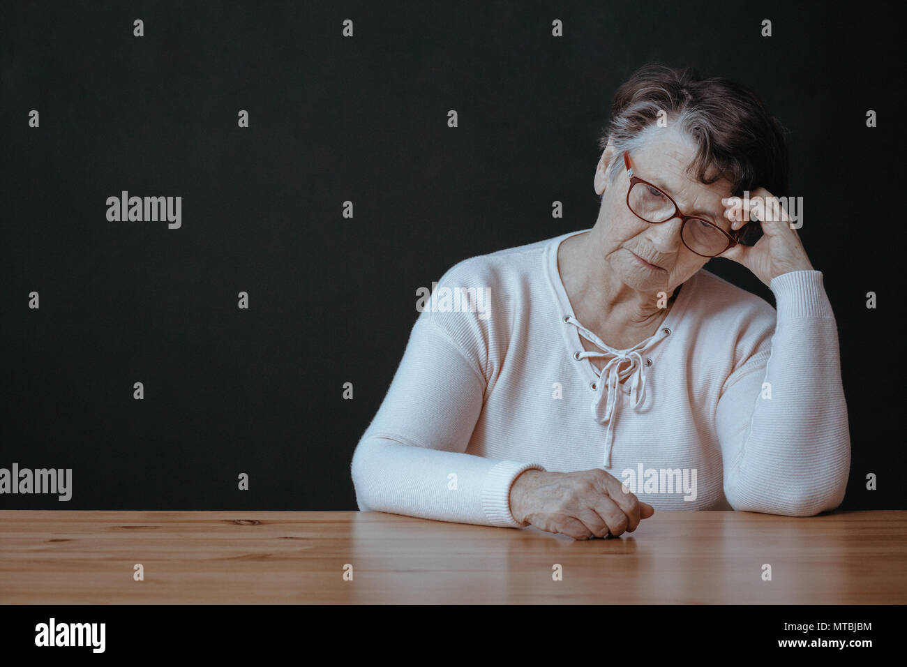 Sad, lonely senior woman sitting beside table - Stock Image