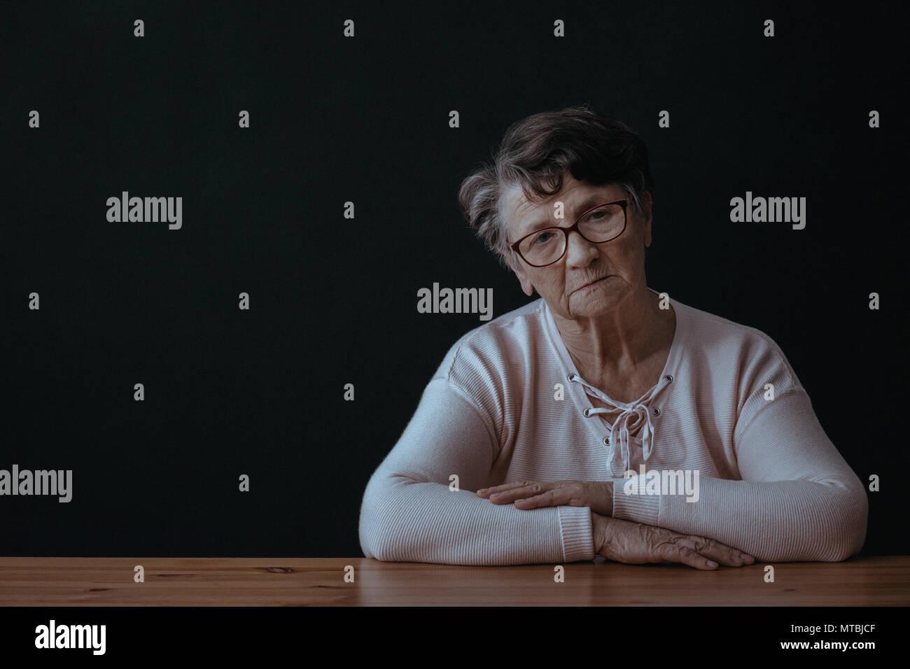 Sad, elderly woman sitting alone beside table - Stock Image
